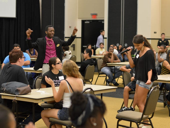 A young lady demonstrates her singing skills to the host and crowd of the Dateabl speed dating event.