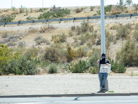 A lone protester wears a mask and holds a sign as many more protesters gather across the street at the corner of East University Avenue and South Valley Drive on Wednesday, April 11, 2018, at the Ramada Palms where U.S. Attorney General Jeff Sessions spoke during the Texas Border Sheriff's Coalition Annual Spring Meeting.