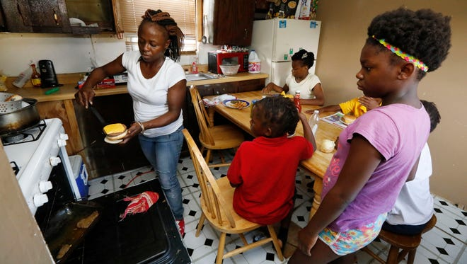 In this July 24, 2017 photograph, Otibehia Allen prepares dinner for her children in their rented mobile home in the same isolated, low-income community of Jonestown, Miss., where she grew up among the cotton and soybean fields of the Mississippi Delta. Her children are on Medicaid, but Allen says a small pay raise meant she lost her own coverage through the federal and state health insurance program.