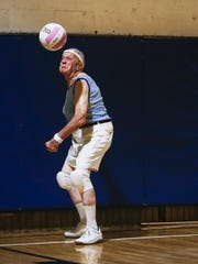 Robert Luscombe serves the volleyball during a game at the Lansing Parks and Recreation's adult volleyball league at Foster Community Center in Lansing.  Luscombe will turn 85 in August.  He has been playing volleyball at Foster Community Center every Tuesday for about 20 years, and has been playing for a total of about 40 years altogether.  He runs his own lawn maintenance company since 1965.
