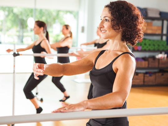 Co-owner Amy Lademann leads participants through a series of exercises during Cardio Barre class at Beyond Motion Studio.