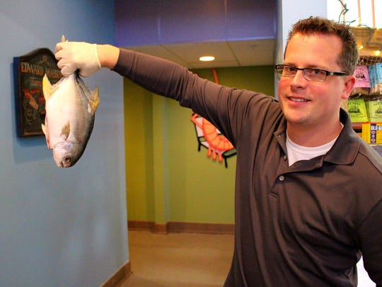 Jim Matzke, seafood procurement specialist at Randy's, shows a fresh Pompano fish.