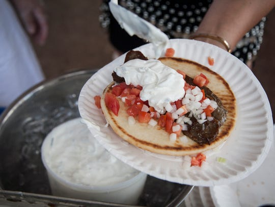 Tara Tsioropoulos adds  tzatziki sauce to gyro during