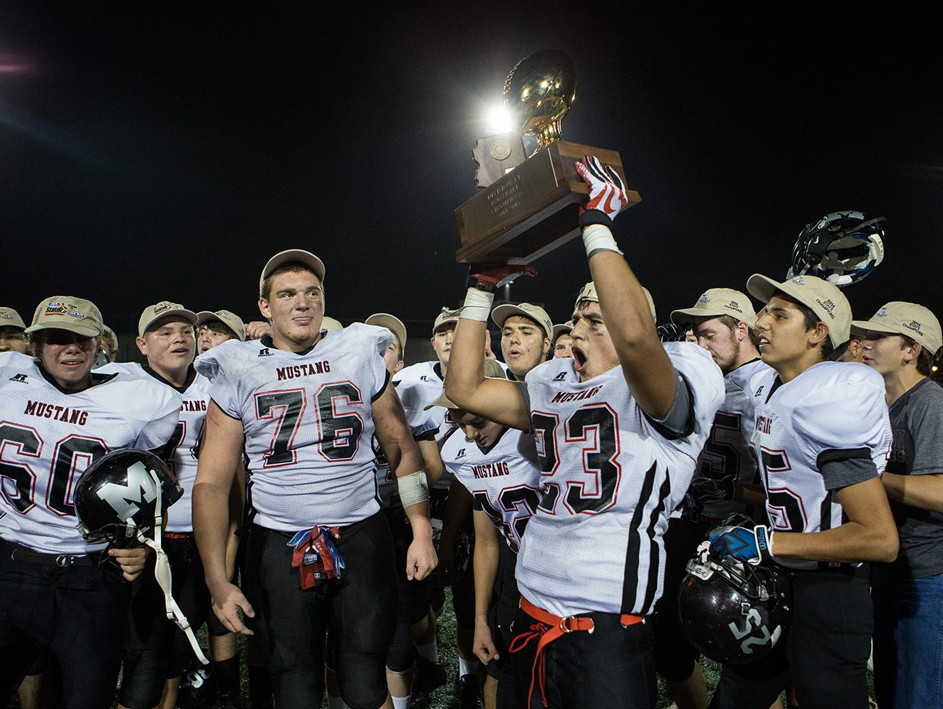 Mogollon junior running back Hunter Cochran holds the trophy and celebrates their win over Bagdad at the Division VI high school football state championship game November 15, 2014 in Phoenix.