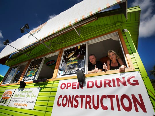 Christina Possiel, part owner of the Lehne Burger on Fort Myers Beach poses for a photo with employee Juri Peplau on Thursday.  She says sales are down 20-50 percent since construction on Estero Boulevard started.   She understands construction needs to be done but wishes there was more communication when it directly impacts her business.