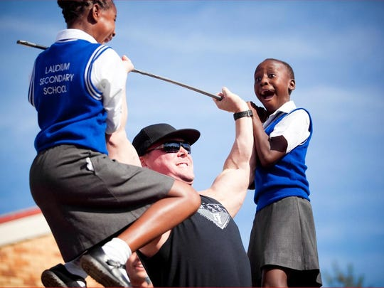 A team Impact member lifts two girls at a school program.