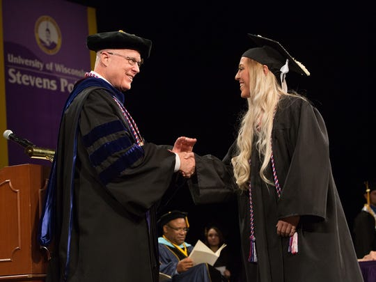 College of Letters and Science graduate Erin Lipski, a sociology major from Stevens Point, shakes hands with Chancellor Patterson as she crosses the stage at the May 21, 2016 morning Commencement ceremony.