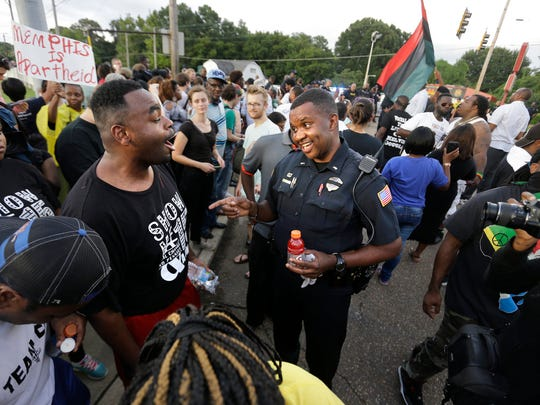 MPD Lt. A. Gardner, center right, tries to calm an displeased crowd including Antonio Blair, center left, as members of the community protest during Graceland's Elvis Candelight Vigil.