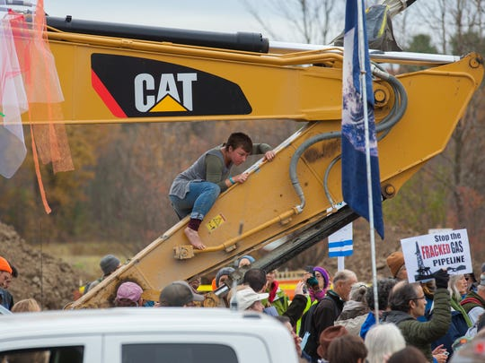 Protesters climbing on construction equipment during