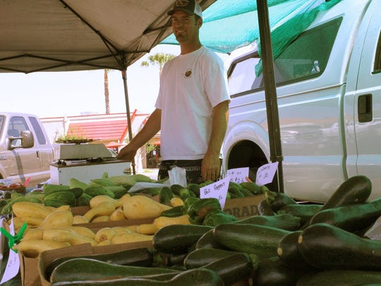 Chris Burlison from Burlison Fruist Stand in Dairyville sells produce at a Redding farmers market.