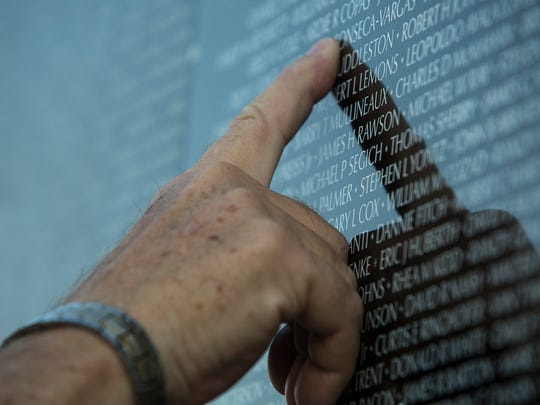 "The Vietnam Memorial ""Moving Wall"" at Mission Springs Park in Desert Hot Springs on June 22, 2017. The wall will be available to the public through the weekend. In this photo, a volunteer points to a name on the wall."