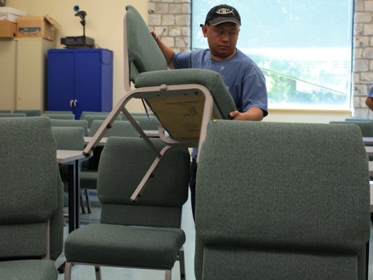 Student worker Andrew Her moves chairs at Simpson University during the summer break.
