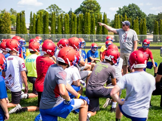 St. Clair High School football coach James Bishop directs the Saints during a pre-season football practice Tuesday. This is Bishop's first year at St. Clair High School.