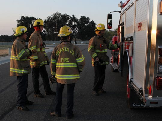 Fire Apparatus Engineer Daniel Whithorn, right, discusses a training exercise with Palo Cedro volunteer firefighters.