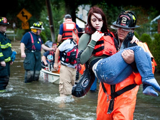 A firefighter rescues a woman who was trapped in her flooded New Milford home in the aftermath of Hurricane Irene in August 2011.