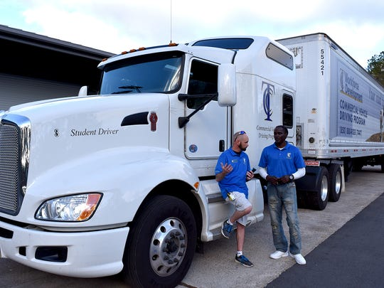 Thomas Paul, lead instructor for TCC's Commercial Vehicle Driving Program, left, talks to recent graduate Eugene Cuff.