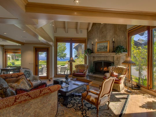 A stone fireplace anchors the great room at residence