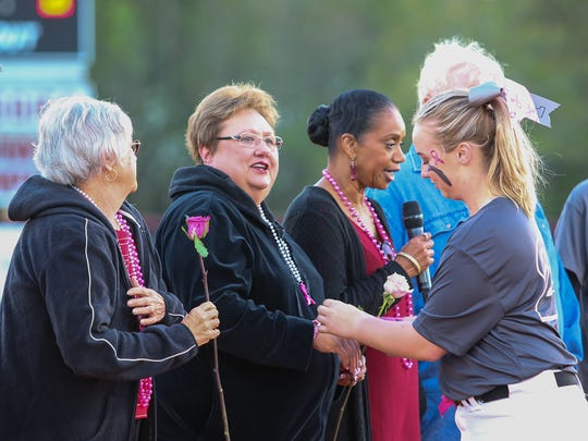 The Tate High softball team gives cancer survivors roses before the start of the 9th annual Strike Out Cancer softball game at Tate High School on Friday, March 23, 2018. Over the years, the event has raised about $100,000 for the American Cancer Society.
