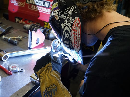 An employee works on a custom-made part at Scott's Hotrods 'n Customs. The California business is moving to Knoxville in April 2018.
