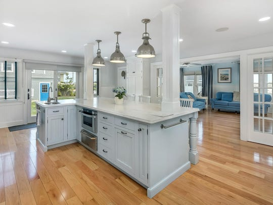 The kitchen features hardwood flooring and a granite stone center island.