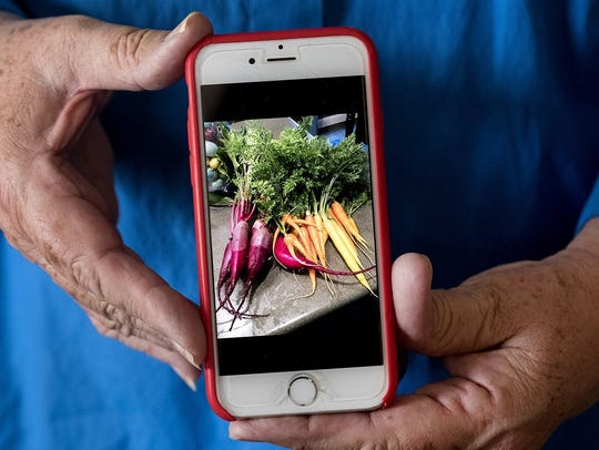Anita McHaney displays a photo of her beets and carrots.