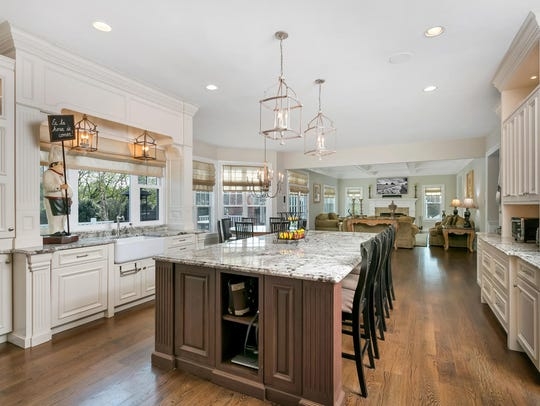 The gourmet kitchen features custom cabinetry and an expansive center island.