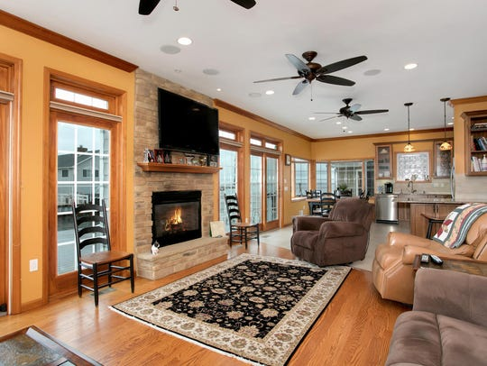 The great room features oversized sliders and a stone fireplace.
