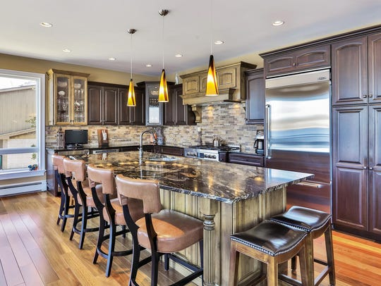 The kitchen offers an expansive granite stone center island with stainless steel appliances.