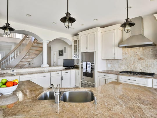 The kitchen features a granite stone center island with a double sink and amazing cabinetry.