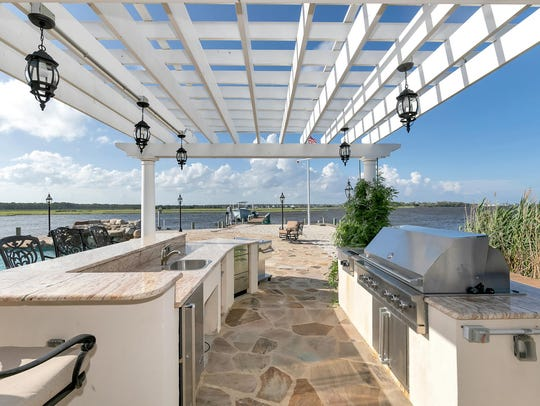 Entertain guest outside that features a dining area and a custom pergola.