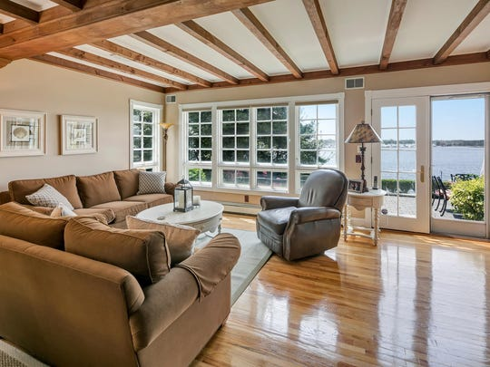 The great room features a set of French doors and beamed ceilings.