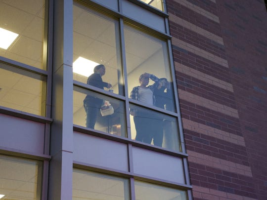 People watch from the window of UNR's Living Learning Community dorm as officers work the area of a shooting Wednesday, Nov. 5, 2014 near the UNR campus.