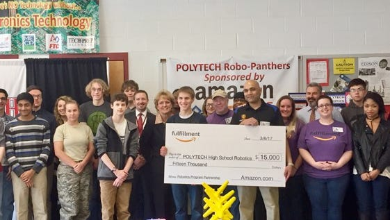 Amazon General Manager Rohan Mendonza presents students from Polytech High School's robotics program with a $15,000 donation.