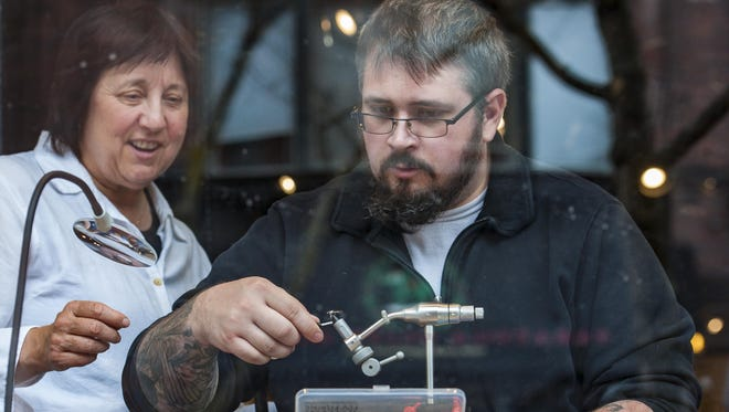 Janie McKenzie, a volunteer with the Green Mountain Chapter of Project Healing Waters Fly Fishing, left, watches as Chris Boutin, a veteran of the U.S. Marine Corps and the Vermont Army National Guard, ties a fly in the window of the Frog Hollow Vermont State Craft Center in Burlington on Thursday, May 5, 2016.  Frog Hollow is hosting a fly fishing-themed exhibit to draw attention to the project which seeks to help disabled current and former members of the military deal with physical and emotional issues.