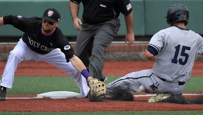 Yale's Alex Stiegler (15) slides safely into third as the ball intended for Holy Cross' Thomas Russo hits Stiegler in the leg in an NCAA college baseball regional game Sunday, June 4, 2017, in Corvallis, Ore. (Mark Ylen/Albany Democrat-Herald via AP)