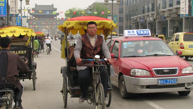 A taxi passes a pedicab in China.