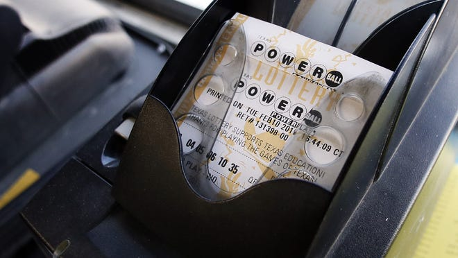 A Powerball ticket sits in the tray dispenser after being printed out for a customer at a Dallas convenience store Tuesday. The jackpot nears $500 million.