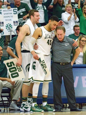 Michigan State coach Tom Izzo (right) is congratulated by guard Denzel Valentine (45) and forward Matt Costello (10) after winning his 500th game in a 99-68 win over the Boston College Eagles at Titan Gym Thursday.