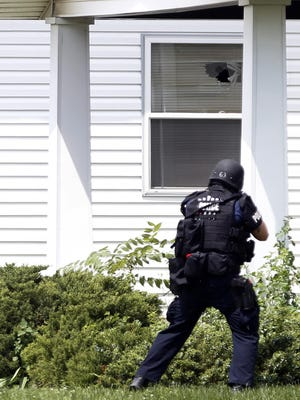 Indianapolis police arrested four individuals, after SWAT officers were fired upon on Friday, Aug 21, 2015, as they tried to serve a narcotics search warrant at a residence in the 10000 block of Baribeau Lane on the city's Eastside. A SWAT team member is shown searching for a suspect in Indianapolis in June 2014.