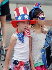 Ava Miller, 8, left, and Sofia Rivera, 10, of Asheville at the downtown Asheville Fourth of July celebration in Pack Square Park in 2012.