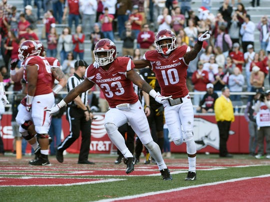 Arkansas running back David Williams (33) celebrates with teammate Jordan Jones after scoring a touchdown against Missouri in the first half of an NCAA college football game Friday, Nov. 24, 2017 in Fayetteville, Ark. (AP