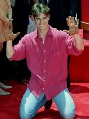 "Actor Tom Cruise holds up his cement-covered hands after he put his signature and hand prints in front of Mann's Chinese Theater 28 June, 1993.  Cruise's lastest movie ""The Firm,"" premieres 28 June in Hollywood.        (Photo credit should read MIKE NELSON/AFP/GettyImages)"