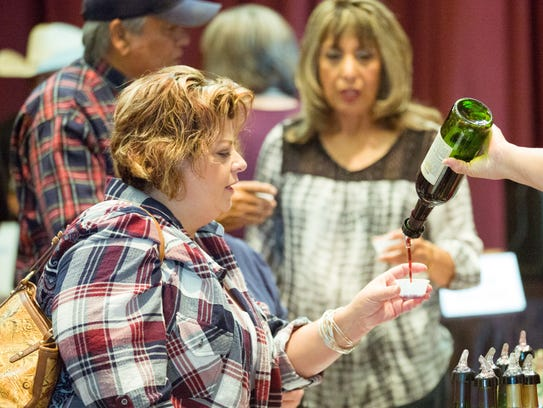 Nicole Warden, of Las Cruces, samples wine from La Esperanza Vineyard and Winery on Saturday, Nov. 18, 2017, during the 4th annual HomeGrown event at The New Mexico Farm & Ranch Heritage Museum.