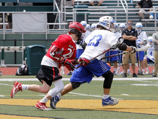 Garrette Briggs of Horseheads takes off with the ball after winning the faceoff against Jamesville-DeWitt's Jack Mulvihill on Saturday during a Class B state quarterfinal at Vestal High School.