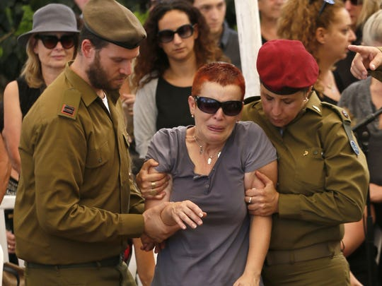 The mother of 20-year-old Israeli Saff Sgt. Amit Yeori mourns by his flower-covered fresh grave during the funeral at the Mount Herzl military cemetery in Jerusalem, on July 27, 2014, after he was killed on July 25 during combat in the southern Gaza Strip. The Islamist Hamas movement continued firing rockets at Israel, despite claims it had accepted a UN request for a 24-hour extension of a humanitarian truce in war-torn Gaza.