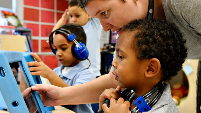 In this file photo Pre-K co-teacher Megan Runk, upper right, works with student Dahjmir Gaines, lower right, on an iPad during afternoon work time at Hannah Penn K-8 School in York, Pa. on Tuesday, Dec. 8, 2015. (Dawn J. Sagert - The York Dispatch)