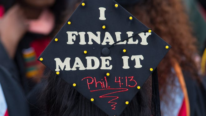 A graduate with a decorated cap enters Alumni Stadium for the 128th commencement ceremony at Delaware State University.