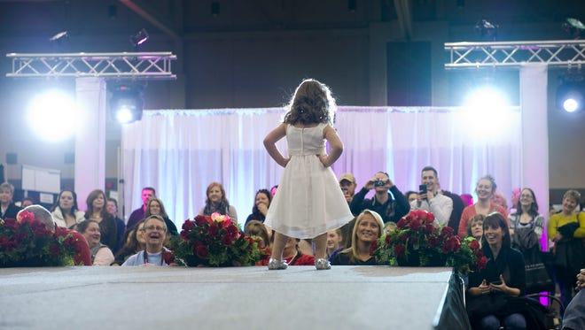 Lily Mizerak, 4, models an outfit for Magic Moments at the Wedding & Prom Expo at the Old National Events Plaza Sunday afternoon.