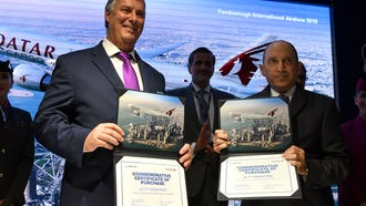 Boeing Commercial Airplanes CEO, Kevin McAllister (left), and Qatar Airways CEO, Akbar Al Baker, display commemorative contracts as they announce the purchase of planes for Qatar Airways' cargo unit at the Farnborough Airshow near London, on July 16, 2018.