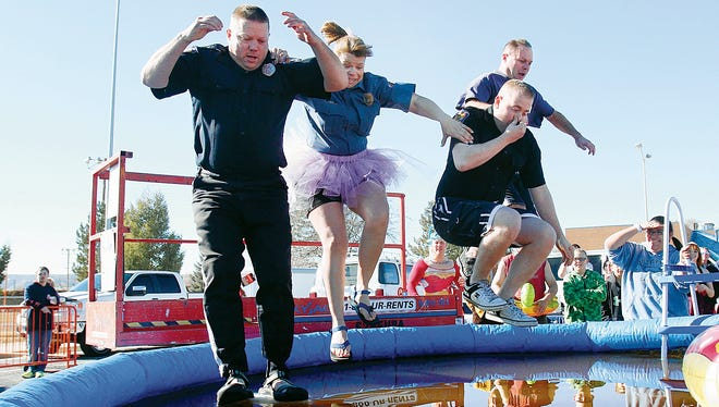 """Members of the """"We Are Torch Run"""" group, represented by members of the Farmington Police Department, take the first jump into a pool during the annual Polar Plunge on Jan. 18, 2014, at the Farmington Recreation Center's parking lot."""